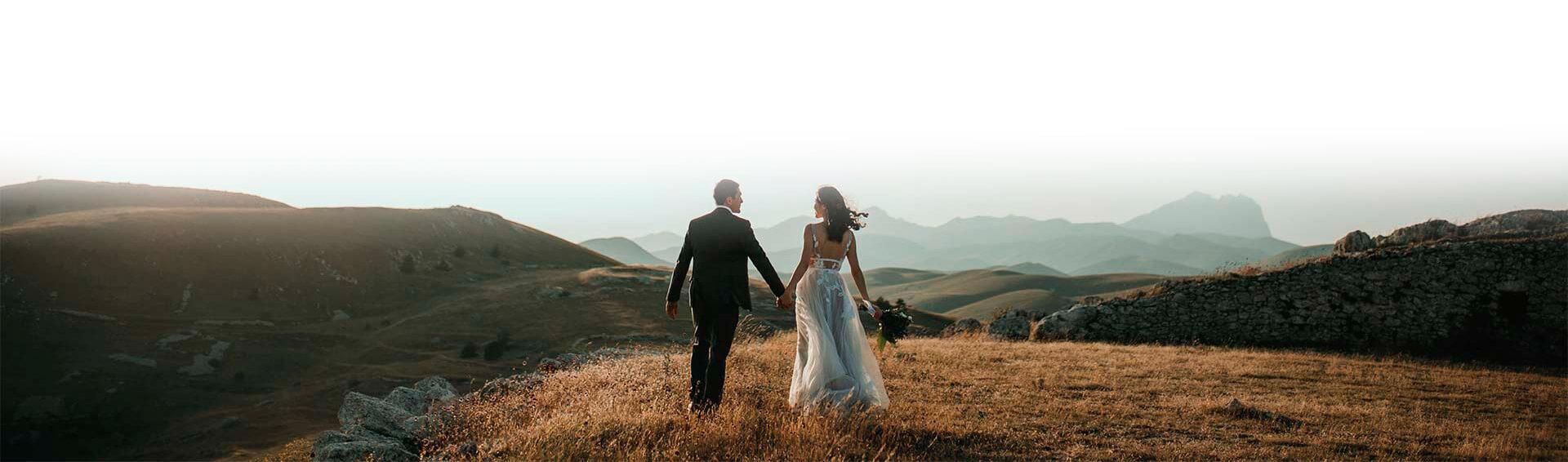 Brautpaar Hand in Hand vor Bergpanorama