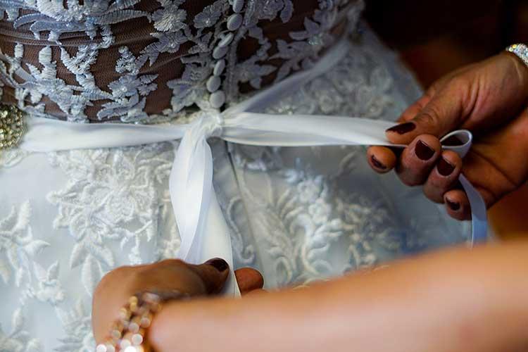 Hände binden ein Hochzeitskleid zu